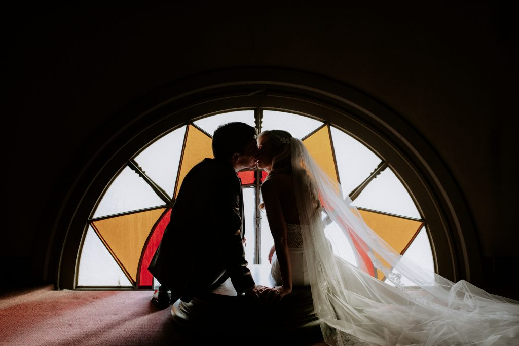 Bride and Groom kiss in front of stained glass window at Catholic Church in St. Louis Missouri.