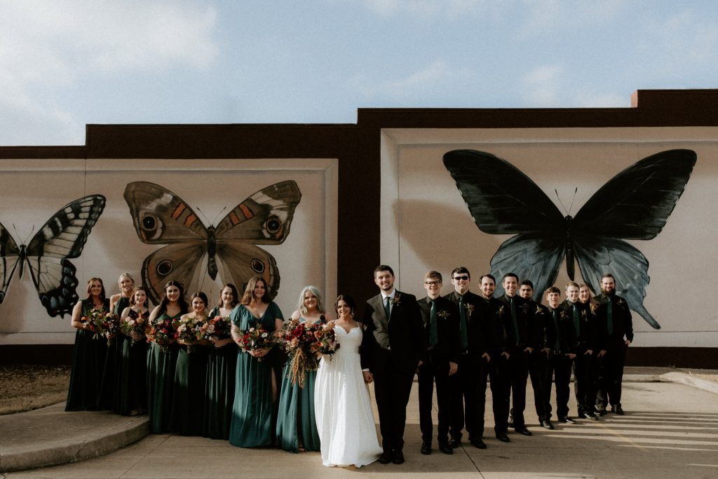 Wedding party posed in front of mural in fort smith, Arkansas