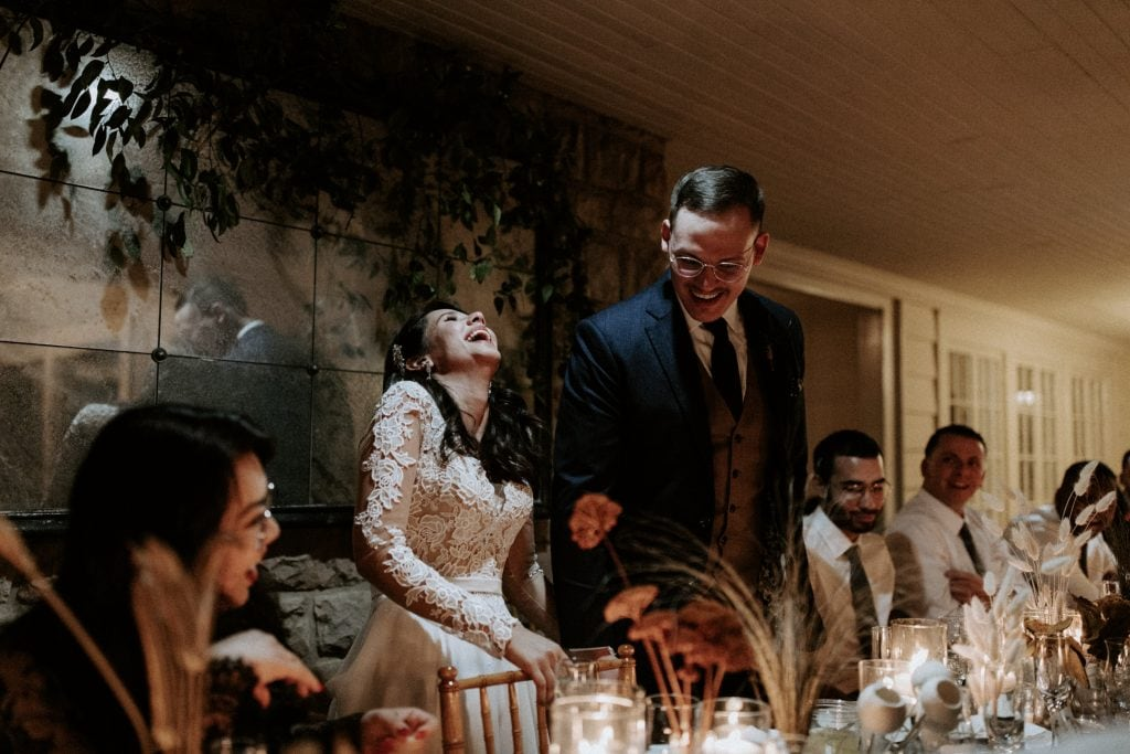 Bride and Groom laughing during the toasts at their reception in Hot Springs.