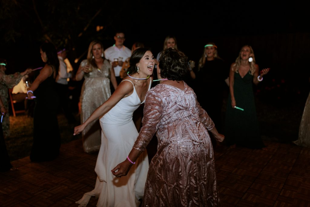 Bride and her mom dancing at their backyard reception in Rogers Arkansas